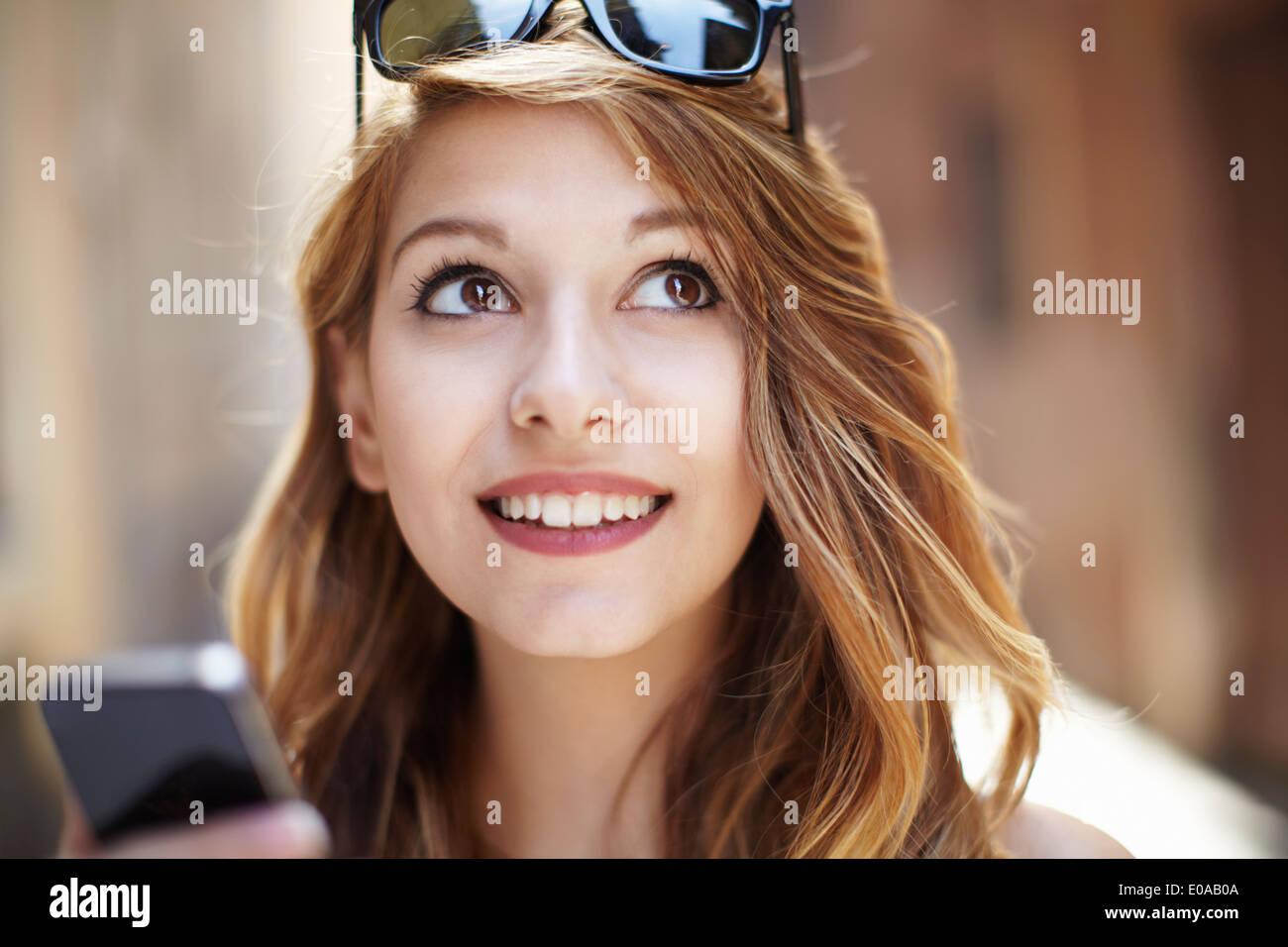 Anspruchsvolle junge Frau blickte auf Straße Stockbild
