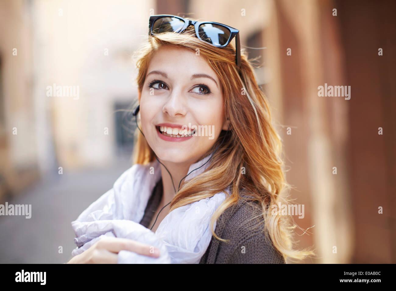 Anspruchsvolle junge Frau blickt zurück auf die Straße Stockbild