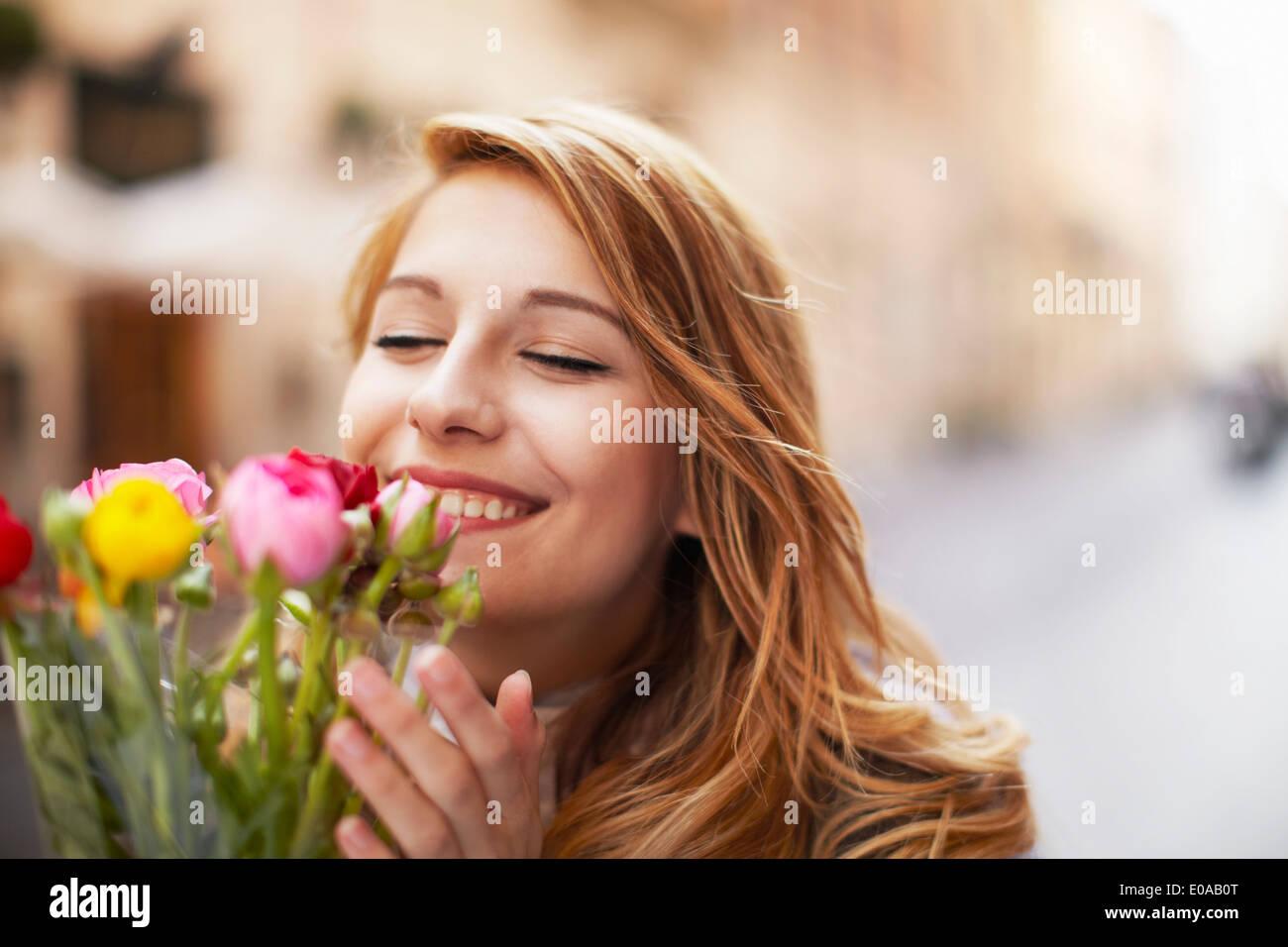 Lächelnde junge Frau riechen einen Blumenstrauß Stockbild