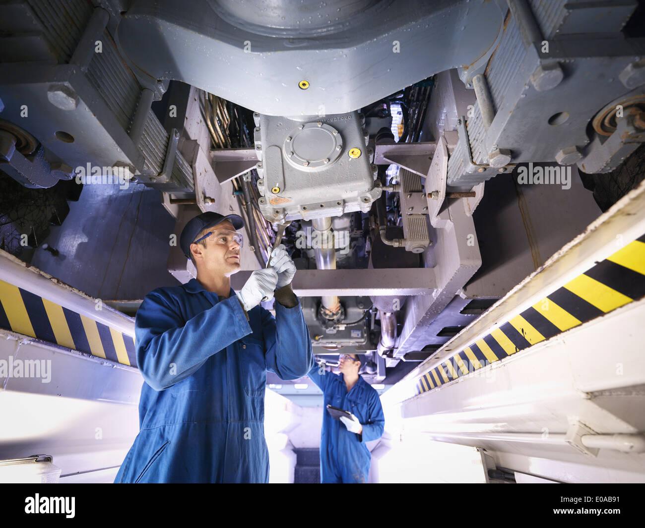 Ingenieure unter LKW Reparaturwerkstatt Stockbild
