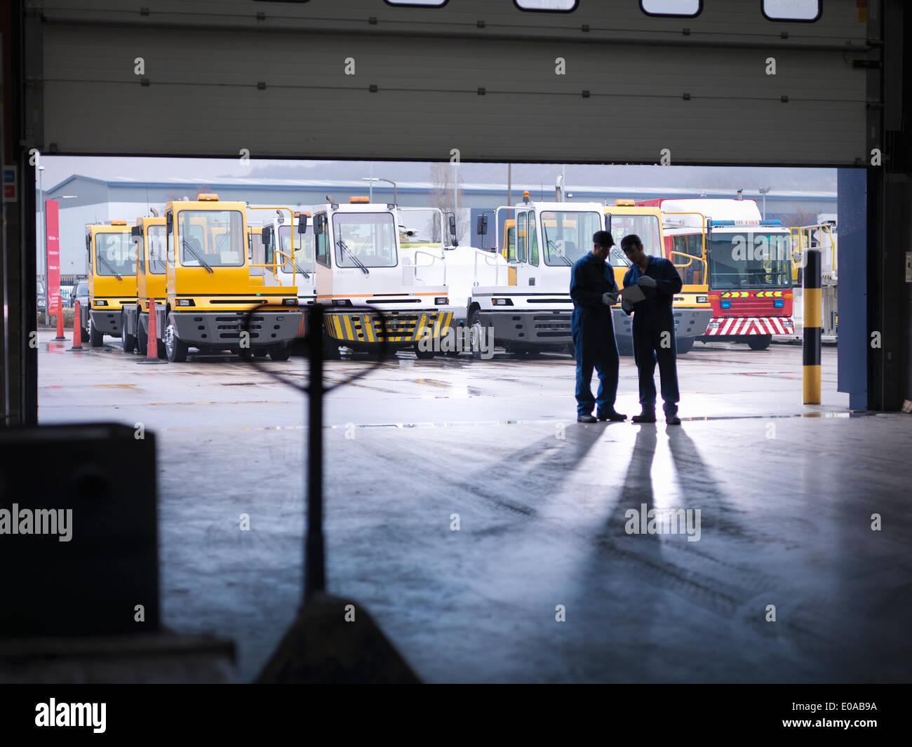 Ingenieure, die Silhouette in Tür in LKW-Reparatur-Fabrik Stockbild
