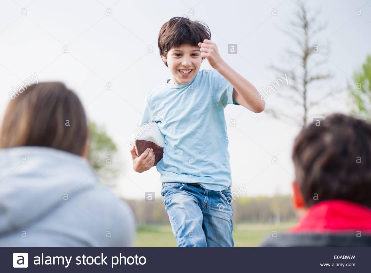 Eltern, die gerade Sohn mit Rugby-Ball im Park laufen Stockbild
