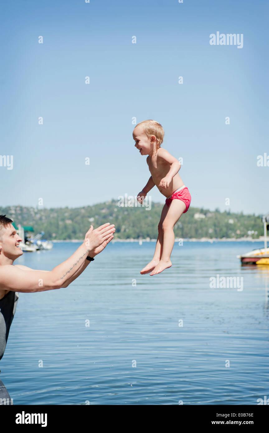 Weiblichen Kleinkind Luft von Vater erwischt Stockbild
