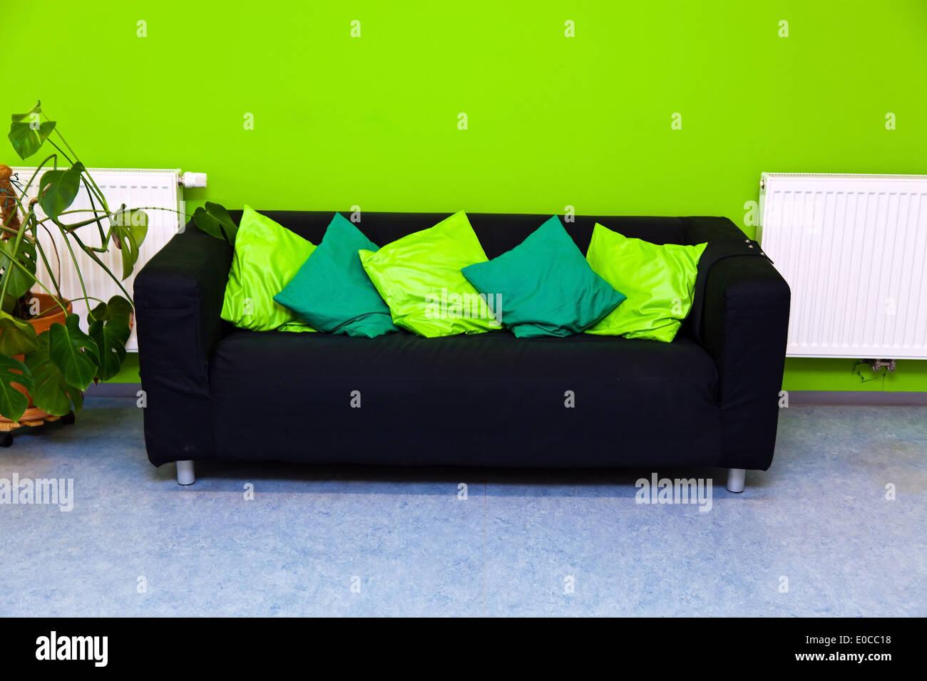 Einem Schwarzen Sofa Im Wohnzimmer Vor Einer Grünen Wand, Eine Schwarzes  Sofa In Einem Wohnzimmer Vor Einer Gruenen Wand