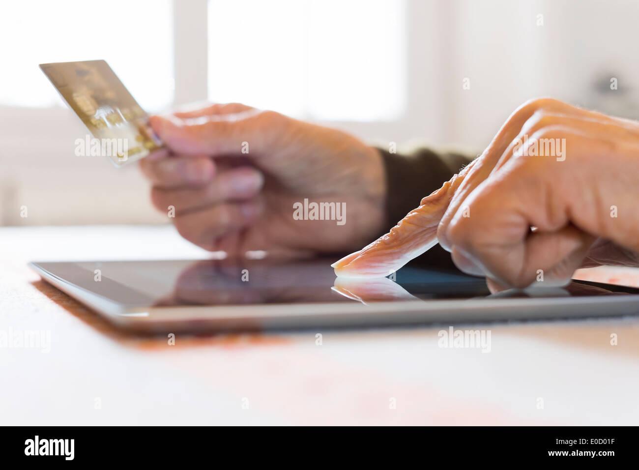 Reife Frauen-digital-Tablette Closeup Hände Plastikkarte Shop im Haus Stockbild