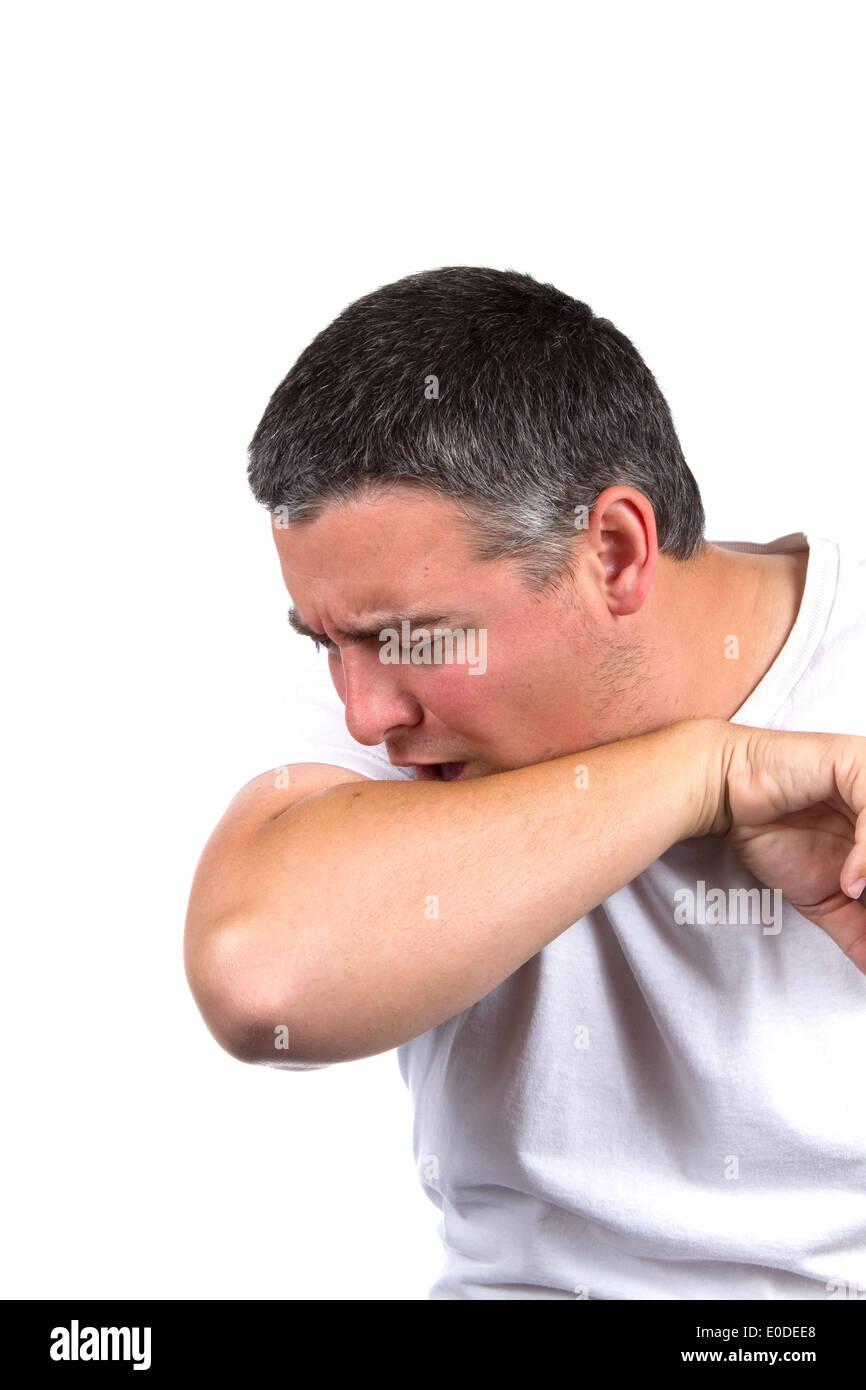 Kranker erwachsener Mann hustet im Inneren seine Ellbogen auf die Ausbreitung von Keimen zu verhindern. Stockbild