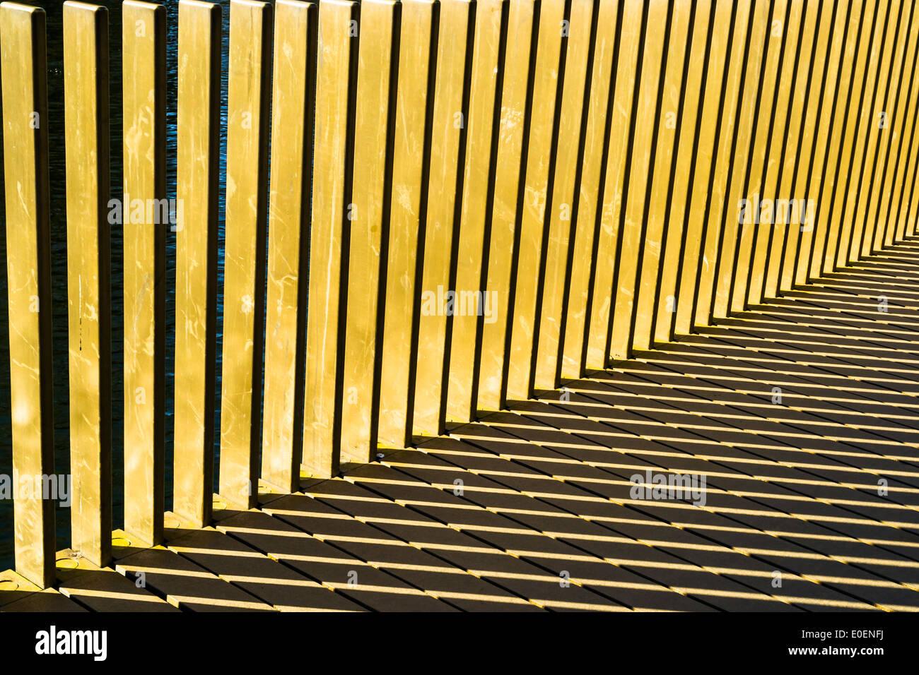 Streifen gebildet durch Sonnenlicht durch Geländer auf einer Brücke - Hintergrund Stockbild