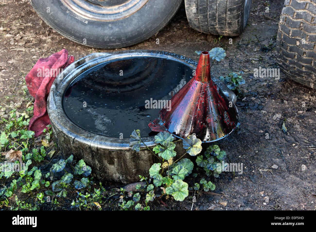 Ölablass pan mit schmutzigen Motoröl verschmutzen Boden & Flora. Stockbild