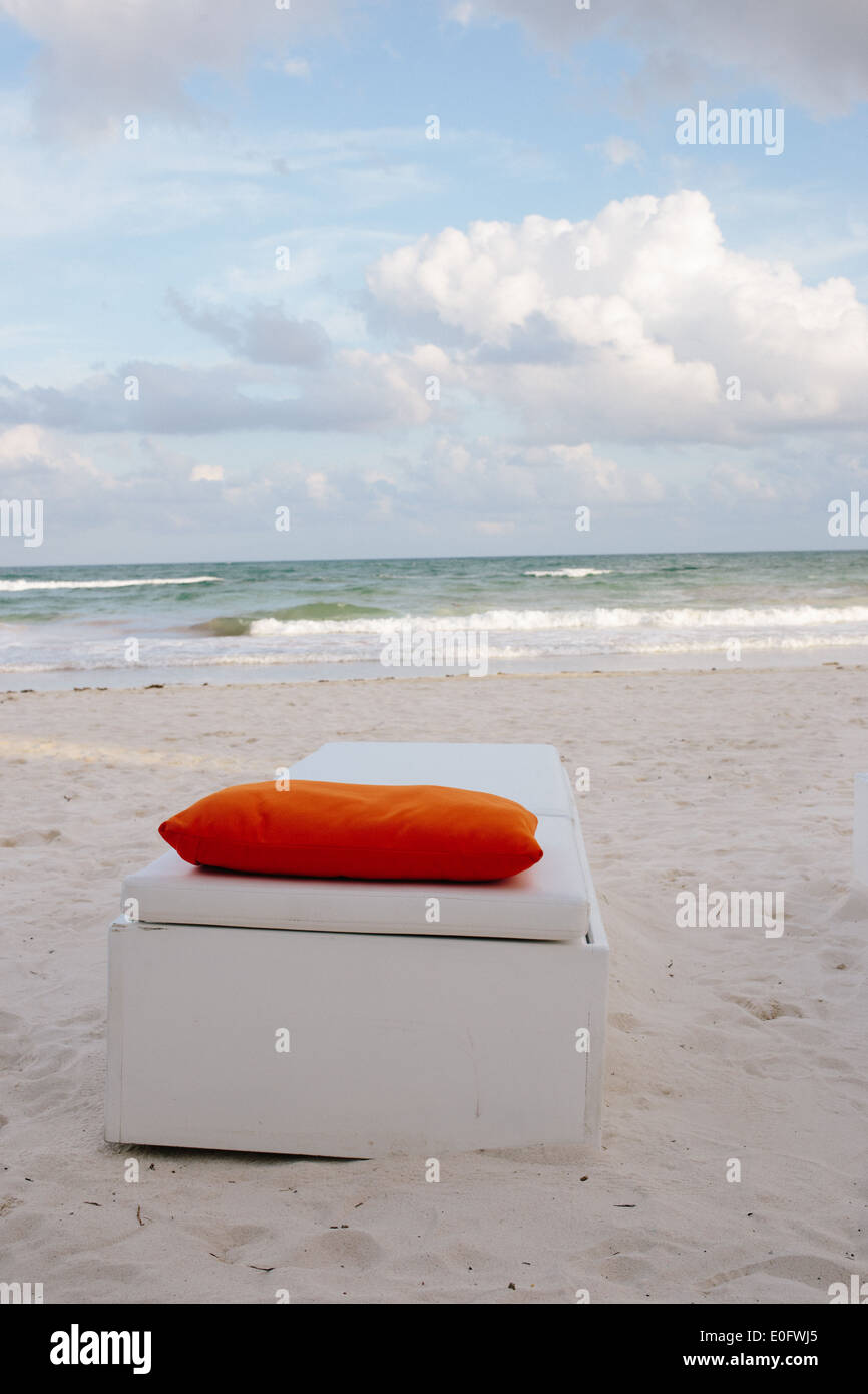 wei e lounge chair mit orange kissen auf sand vor ozean in tulum mexiko stockfoto bild. Black Bedroom Furniture Sets. Home Design Ideas