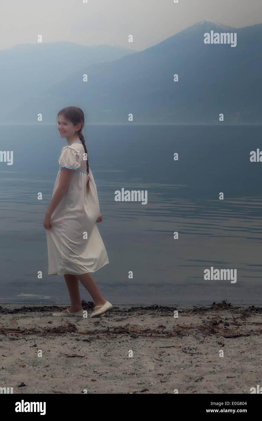 eine Mädchen in einem Kleid tanzt am See Stockbild