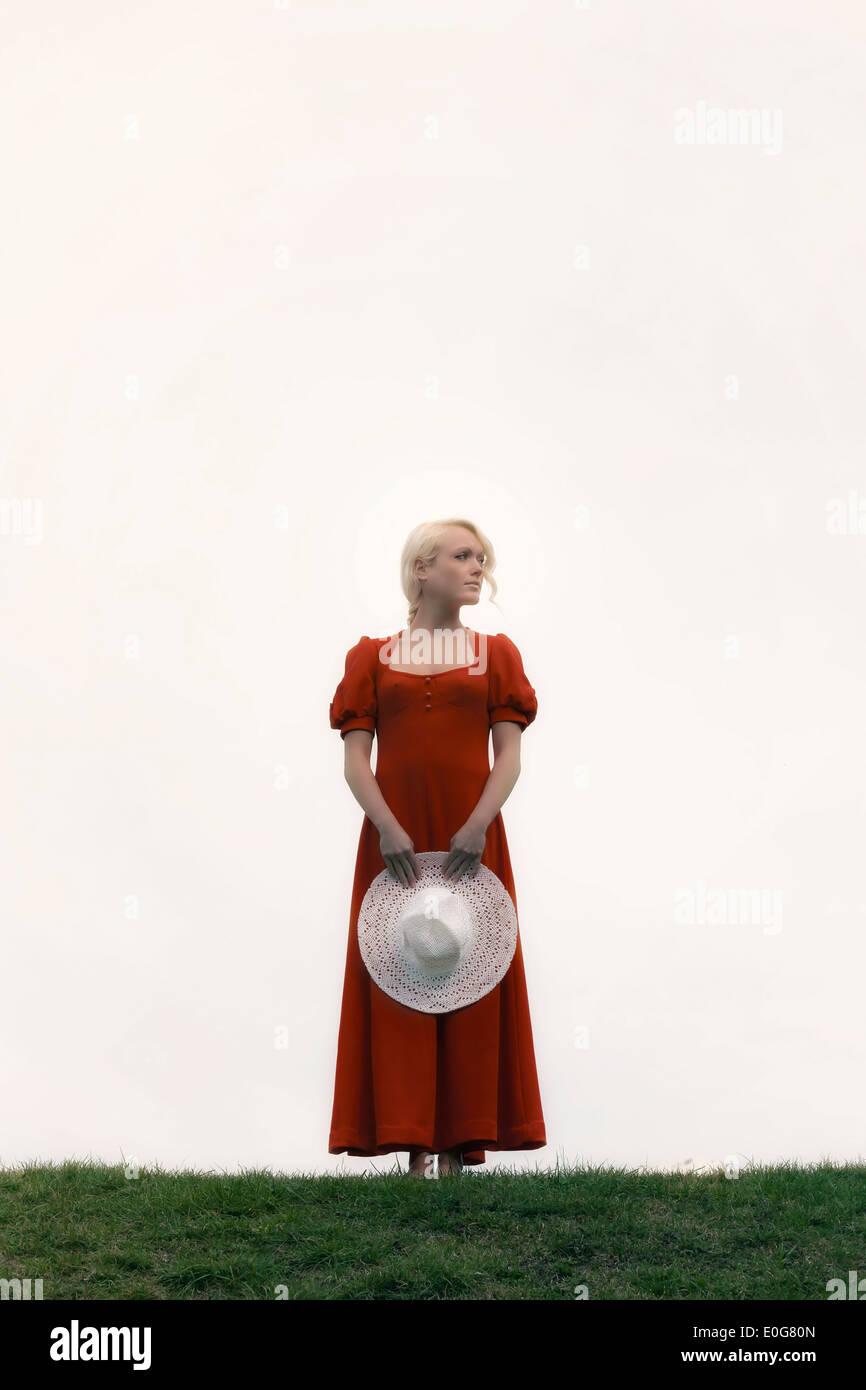 eine Frau in einem roten Kleid mit einem weißen Sonnenhut Stockbild