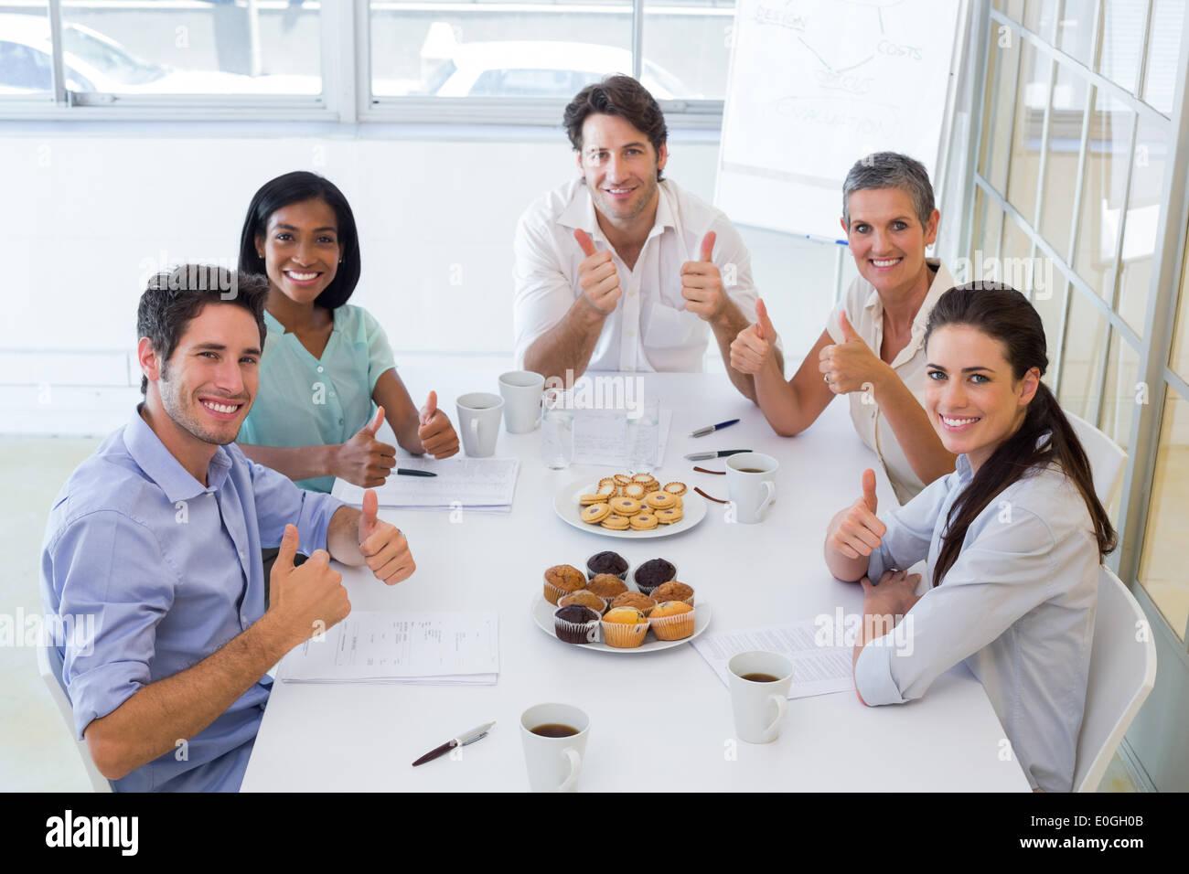 Business-Leute Essen Muffins geben Daumen hoch für Kamera Stockbild