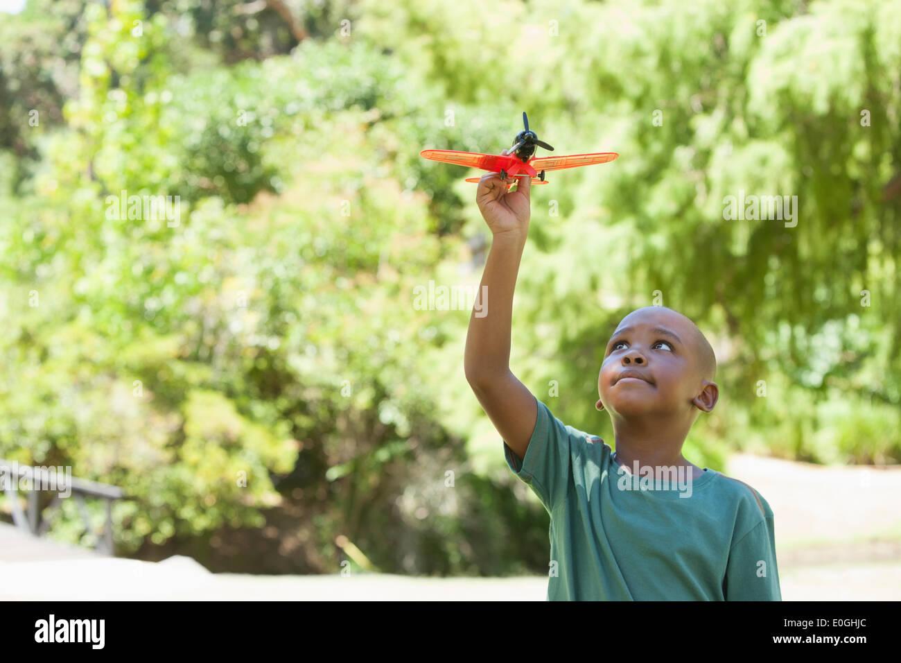 Glückliche kleine Junge Spielzeugflugzeug fliegen Stockbild