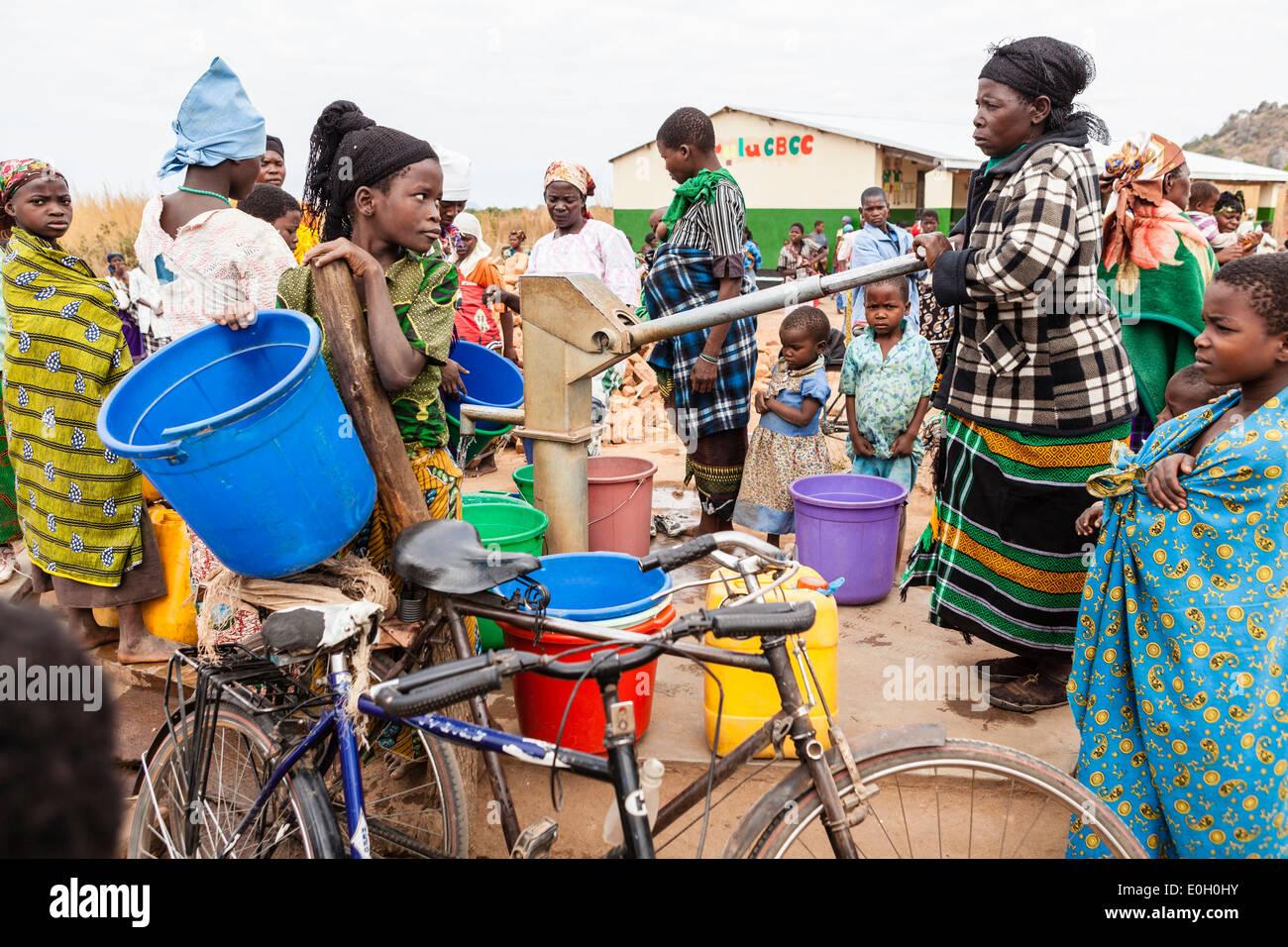 Frauen am Brunnen, Pumpe vor einer Schule im Dorf Machinga Peheriya, Malawi, Afrika Stockbild