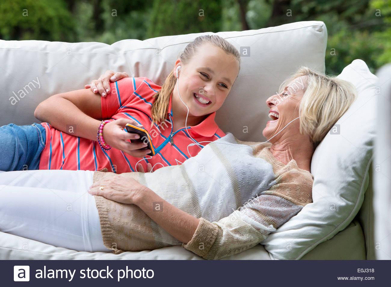 Lächelnden Großmutter und Enkelin Verlegung auf Outdoor-Sofa mit MP3-player Stockbild