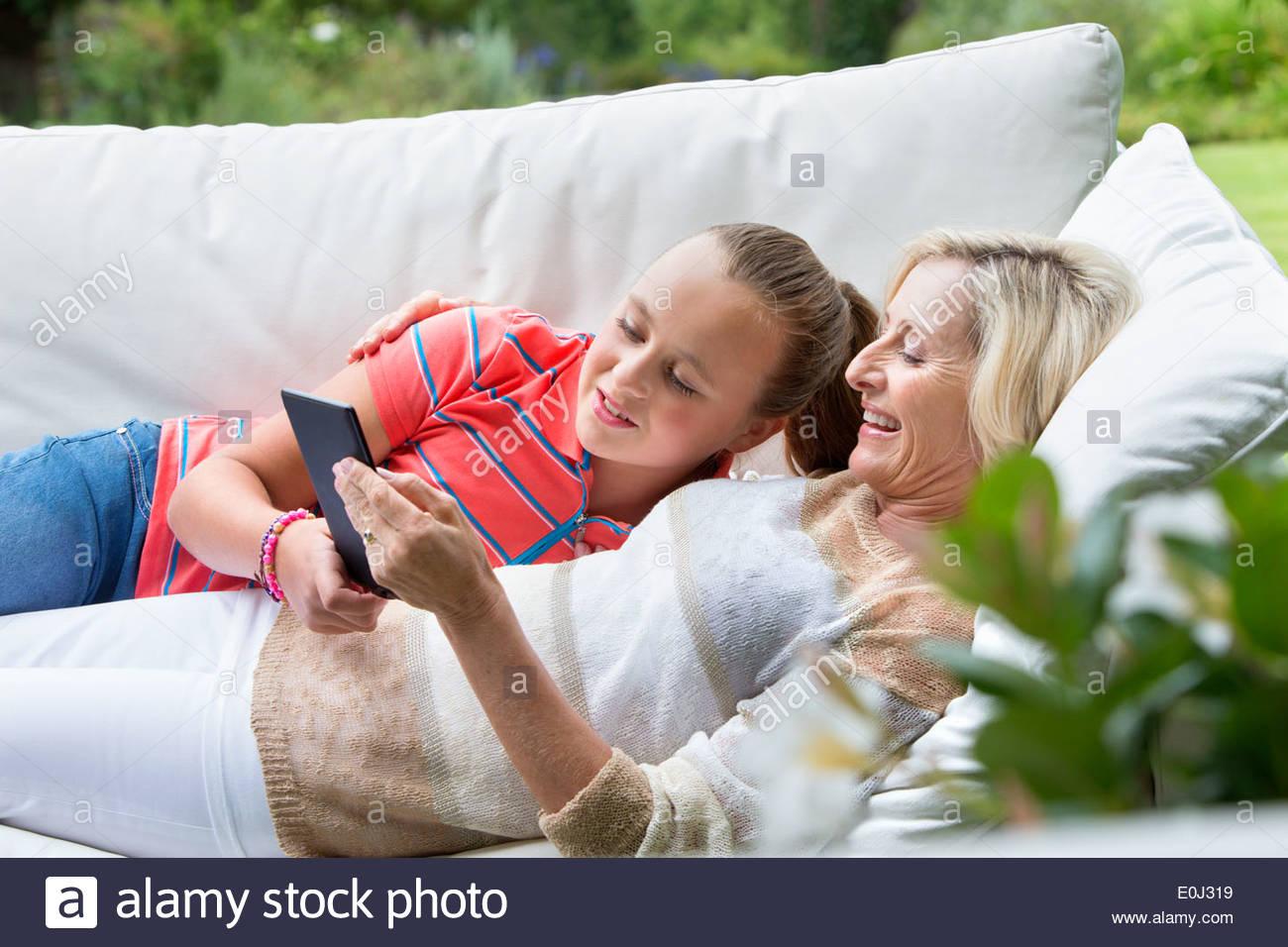 Lächelnden Großmutter und Enkelin Verlegung auf Outdoor-Sofa mit digital-Tablette Stockbild