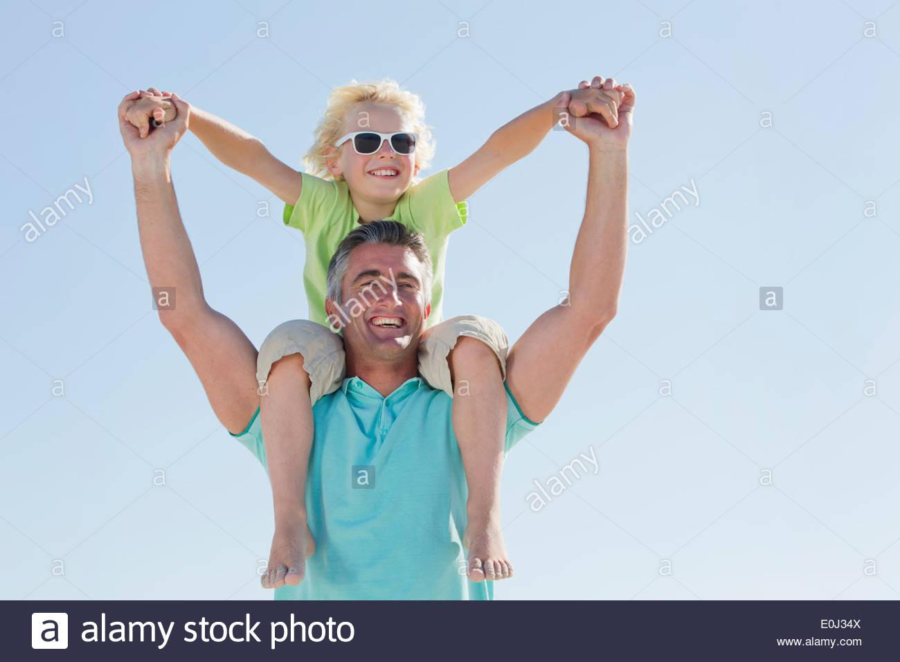 Glücklicher Vater Sohn auf den Schultern tragen Stockbild