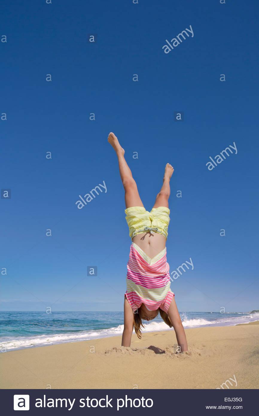 Mädchen tun Handstand am Sonnenstrand Stockbild