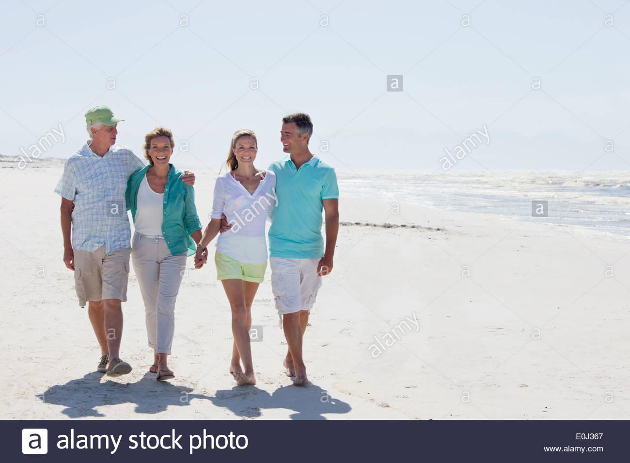 Glückliche Paare, die zu Fuß am Sonnenstrand Stockbild