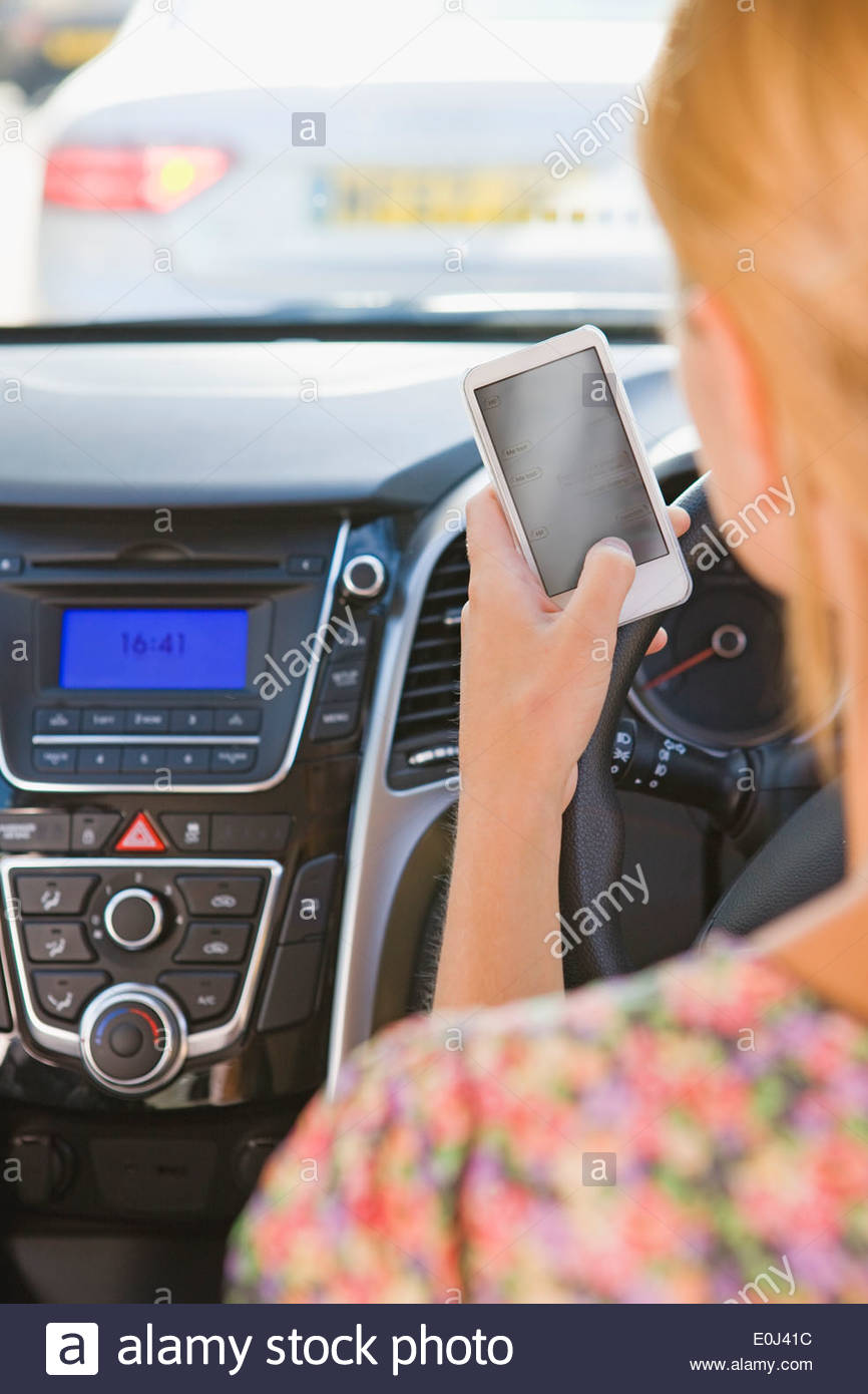 Fahrerin SMS während der Fahrt Stockbild