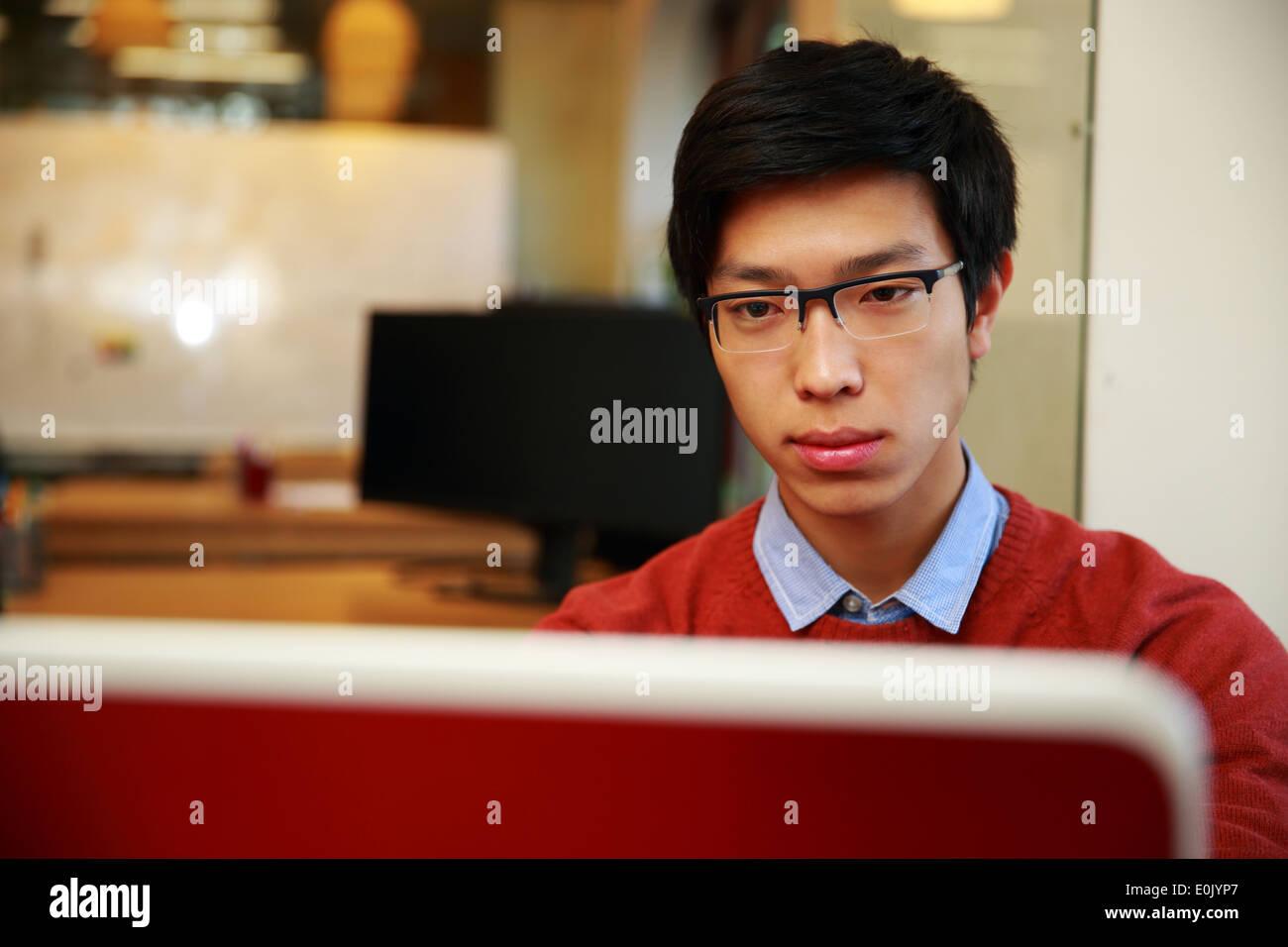 Junge asiatische Mann in Gläsern auf laptop Stockbild