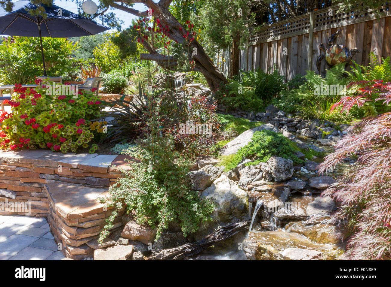 Wasserstrahl Funktion Mit üppiger Vegetation In Einen Schön Angelegten  Garten Mit Gestapelten Steinplatten Stockbild