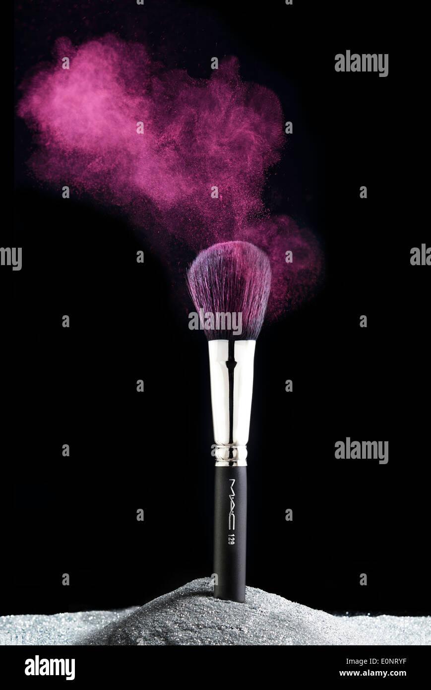 MAC Pinsel mit lila Pulver und Glitzer Produkt High Fashion Make-up und Schönheit Stockbild
