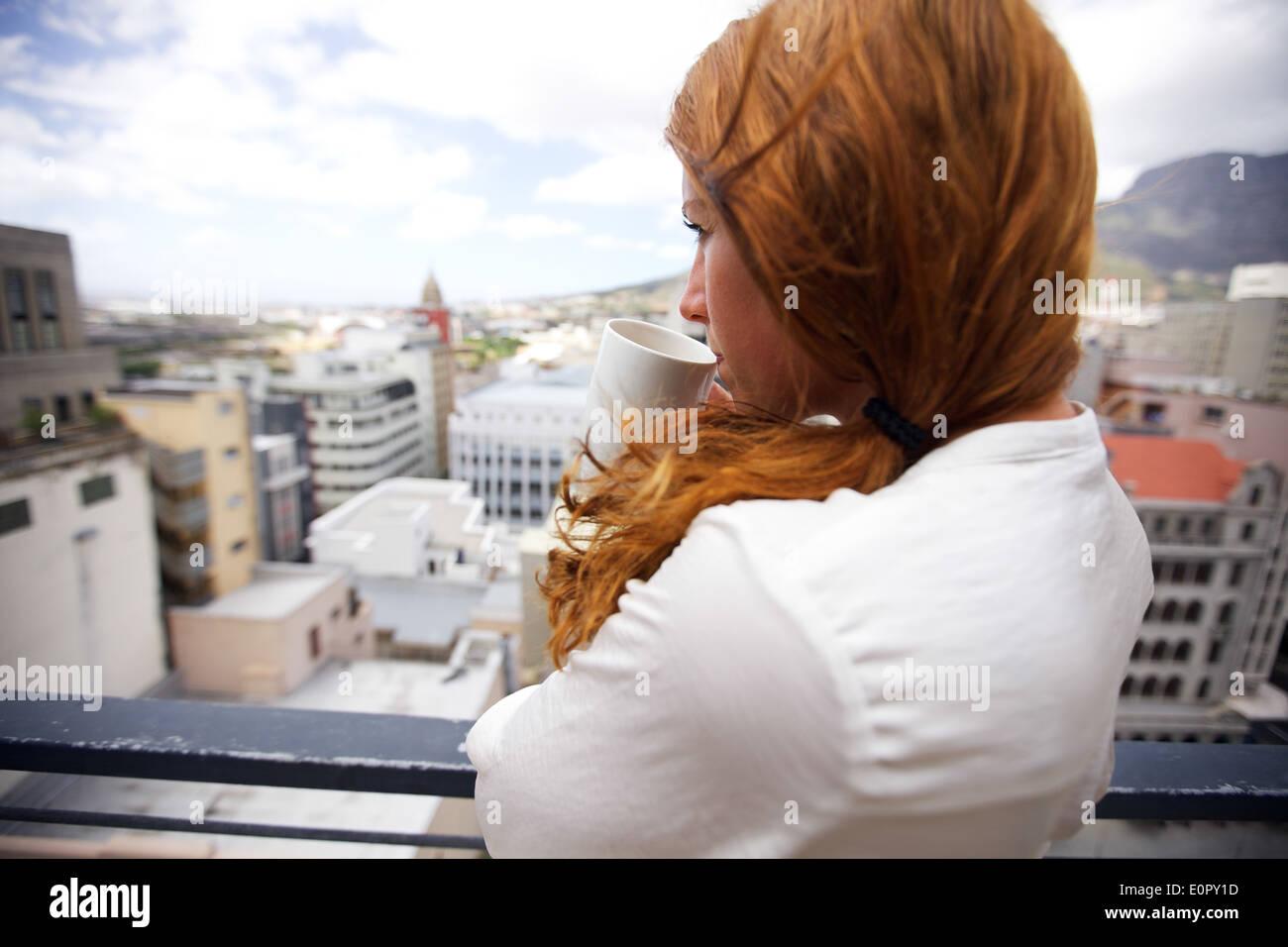 Attraktive Brünette steht auf einem Balkon mit einer Tasse Kaffee. Junge Frau mit Blick vom Balkon beim Kaffeetrinken. Stockfoto