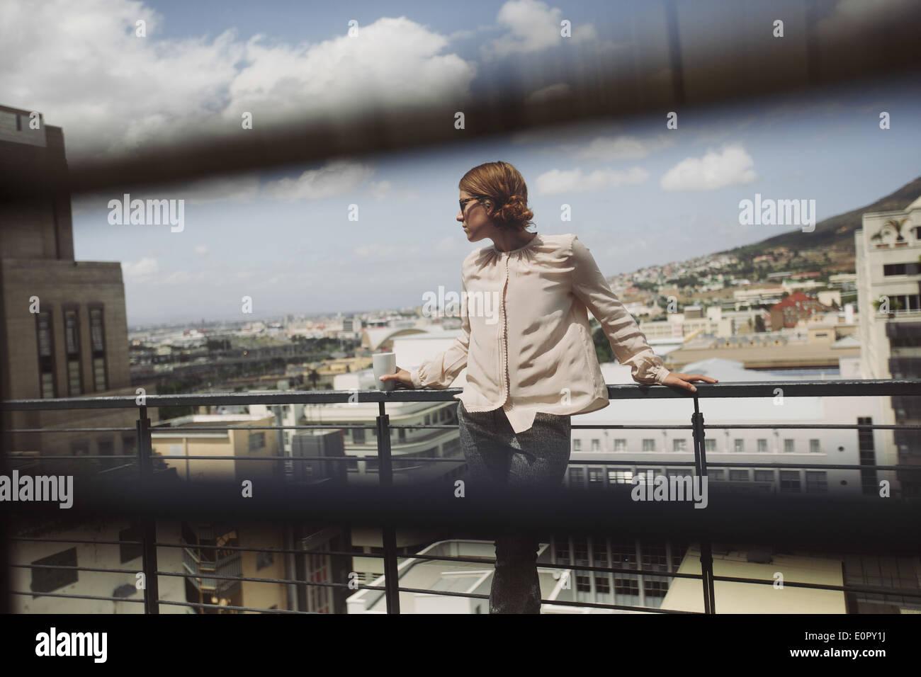 Bild durch Fenster Jalousien von eine junge Frau posiert auf einem Balkon mit Blick auf die Stadt. Hübsche Stockbild