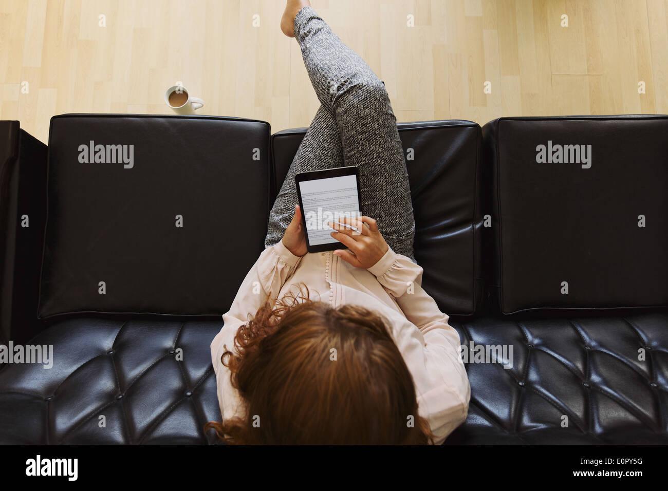 Draufsicht der junge Brünette mit digital-Tablette beim Sitzen auf einer Couch. Weiblich, ein Buch zu lesen Stockbild