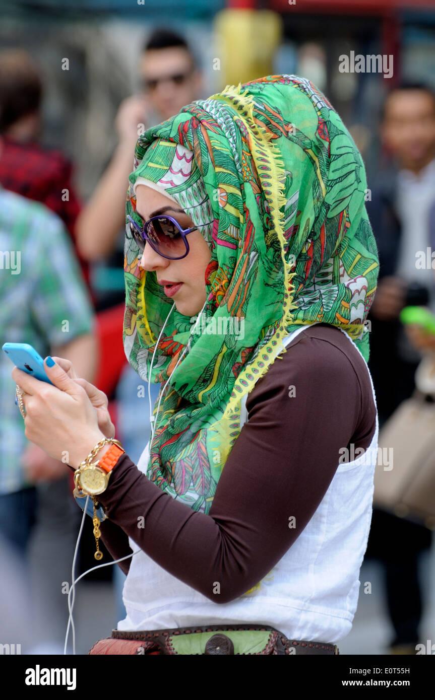 London, England, Vereinigtes Königreich. Junge muslimische Frau in einer bunten grünen Kopftuch Stockbild