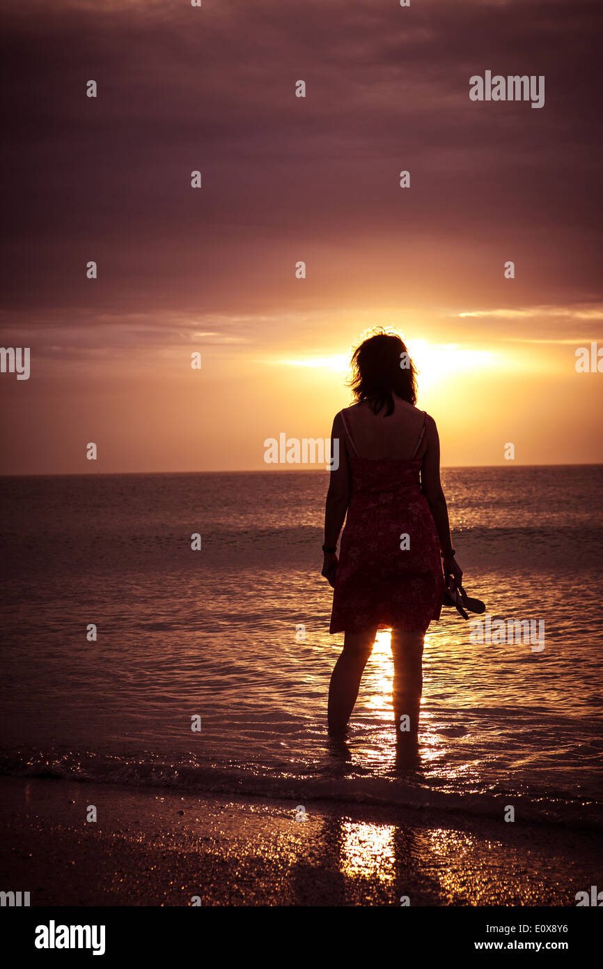 Frau allein am Strand bei Sonnenuntergang Stockbild