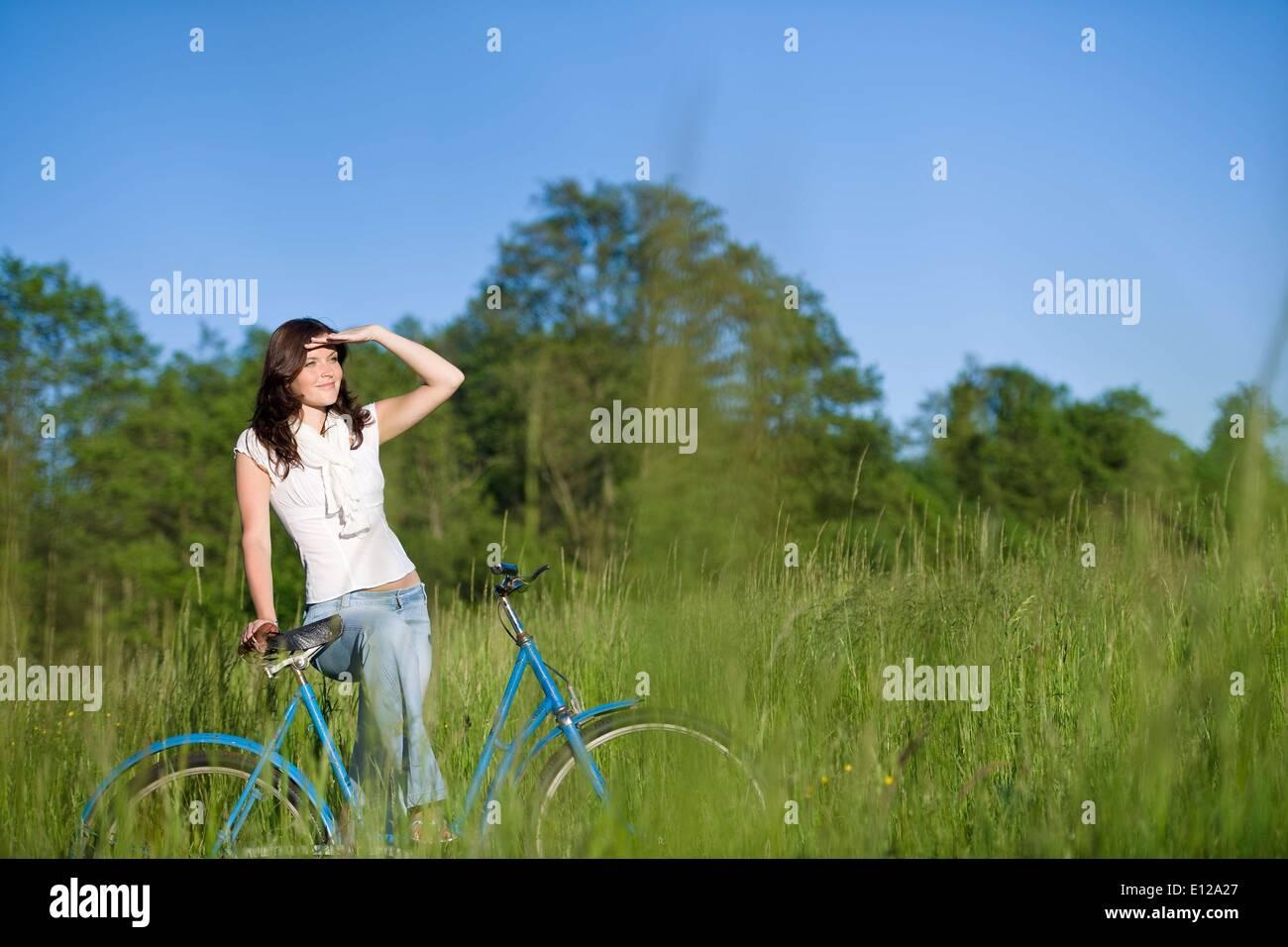 5. Juni 2010 - 5. Juni 2010 - Frau mit altmodischen Fahrrad im Sommerwiese an sonnigen Tag Stockbild
