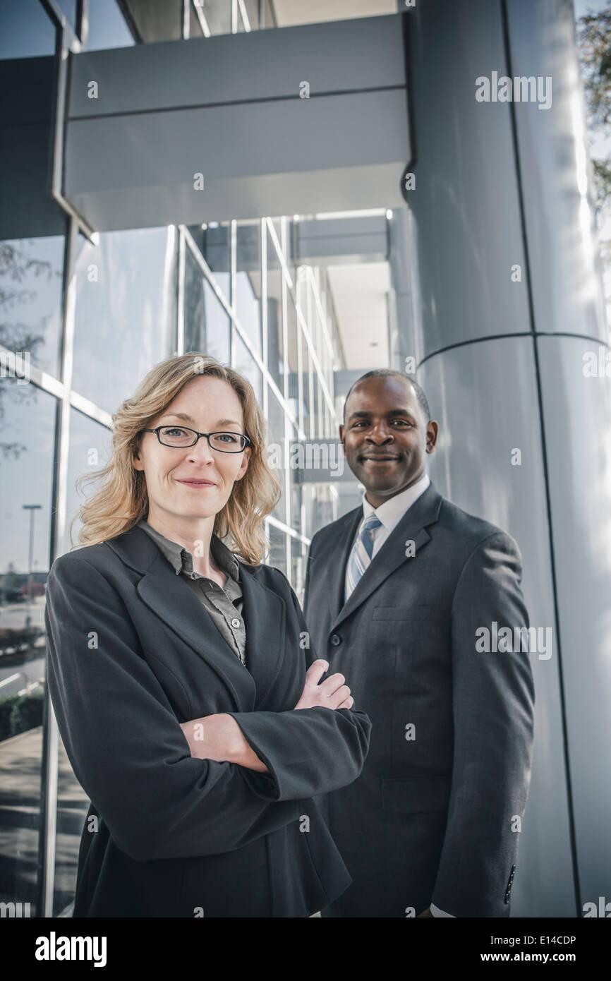 Business-Leute Lächeln Außenseite Bürogebäude Stockfoto
