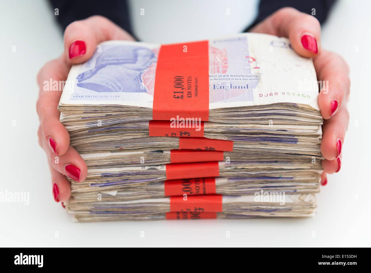 Eine Frau hält £1000 Bündel von britischen Pfund Sterling. Stockbild