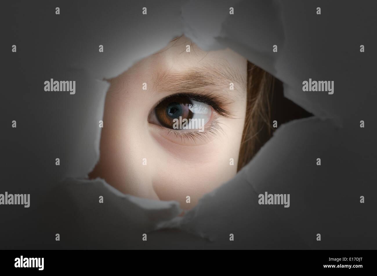 verängstigtes Kind ist durch ein Loch in der Wand Spionage. Stockfoto