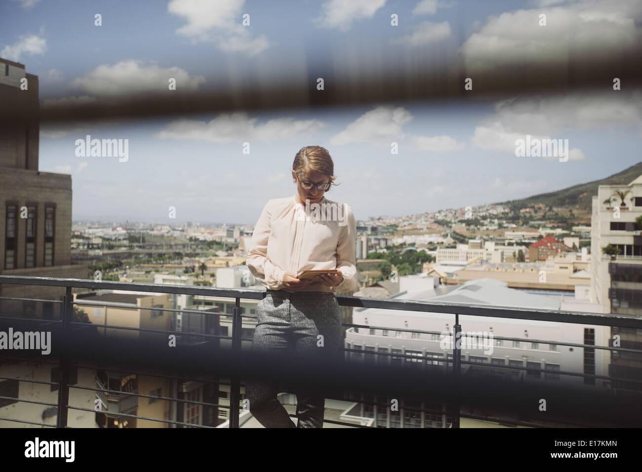 Bild durch Fenster Jalousien von einer jungen Frau, die mit digital-Tablette auf einen Balkon mit Blick auf Stadt Stockbild