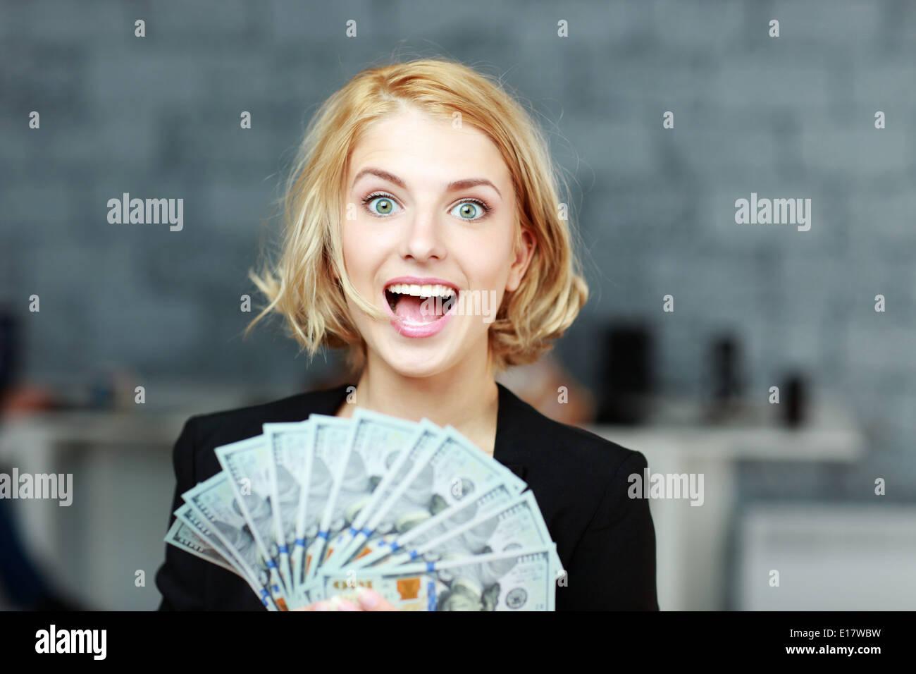 Junge Geschäftsfrau hält Geld mit Freude Stockbild