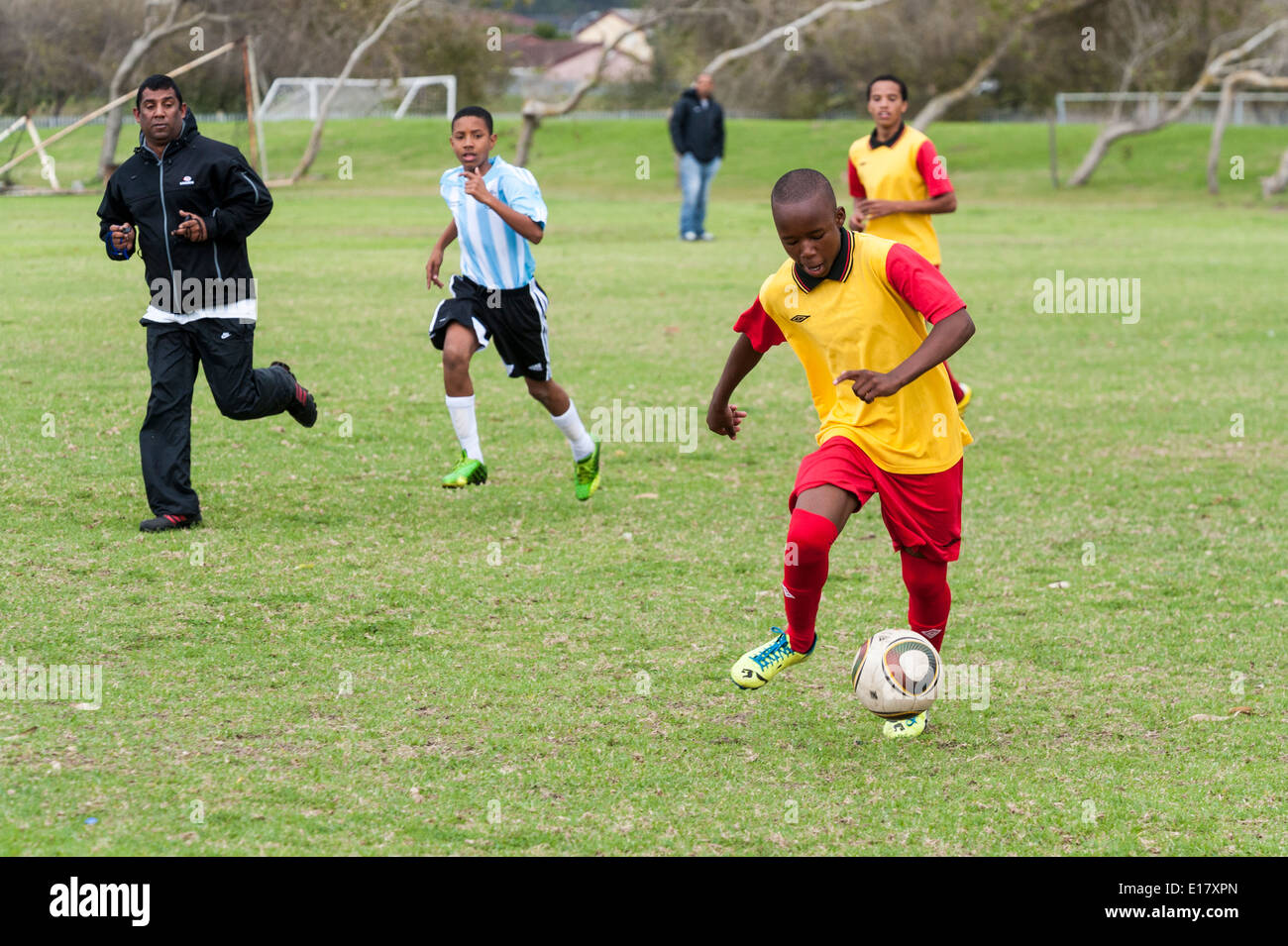 Football-Spieler läuft mit dem Ball, Schiedsrichter beobachten, Cape Town, Südafrika Stockbild