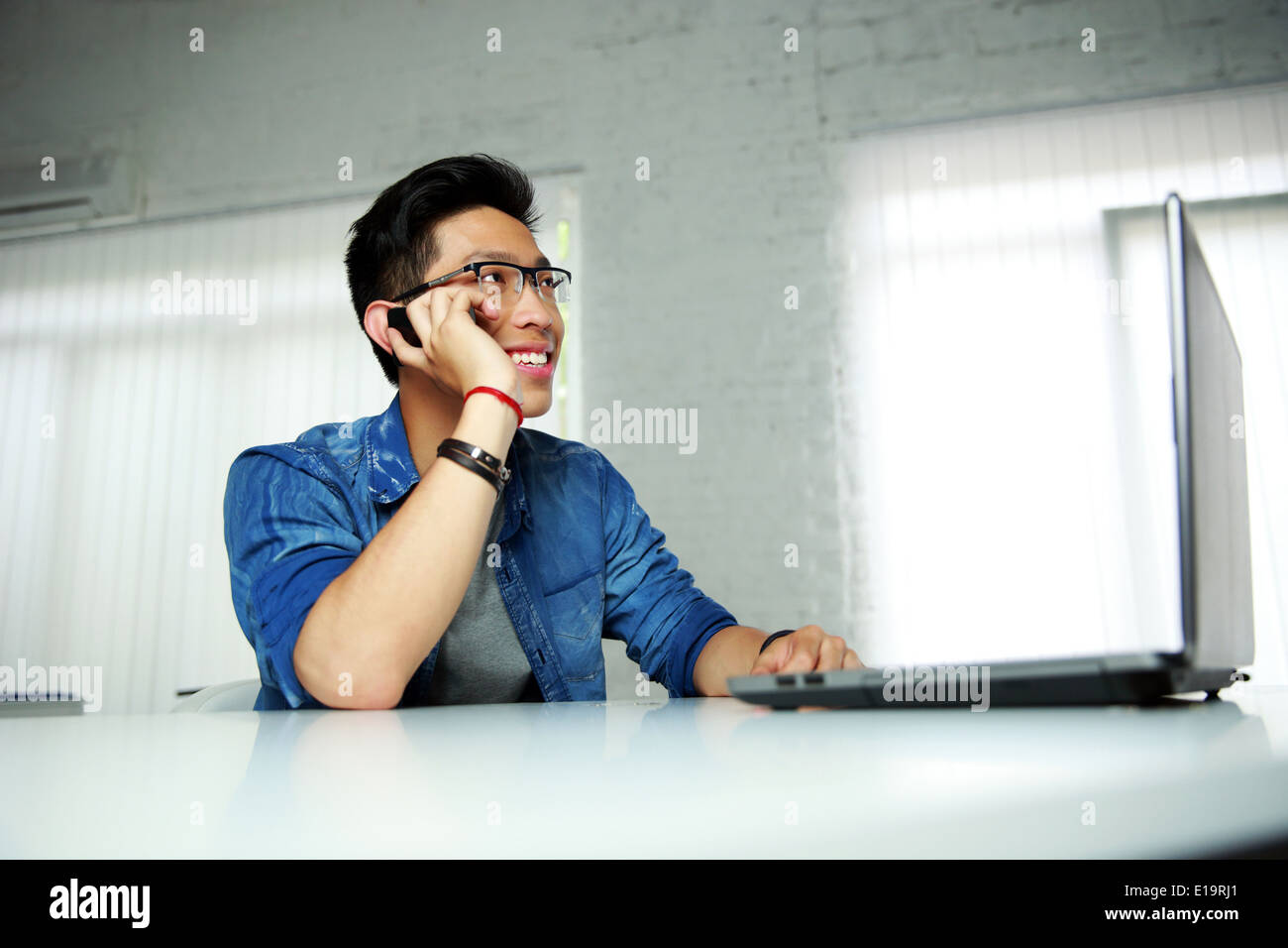 Glücklich asiatischer Mann sitzt an seinem Arbeitsplatz im Büro und am Telefon sprechen Stockbild
