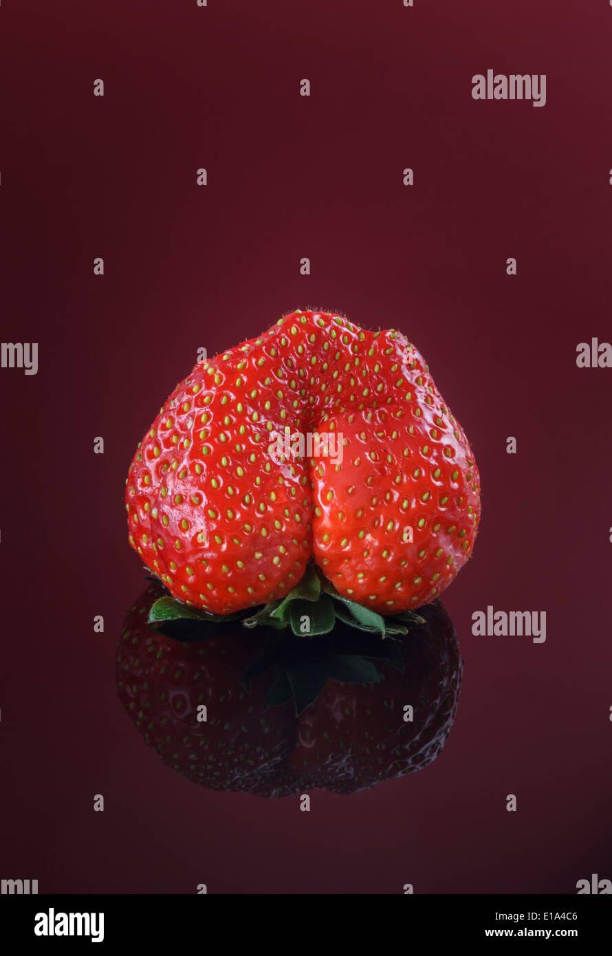 Einzigen frischen Erdbeere auf rotem Grund Stockbild