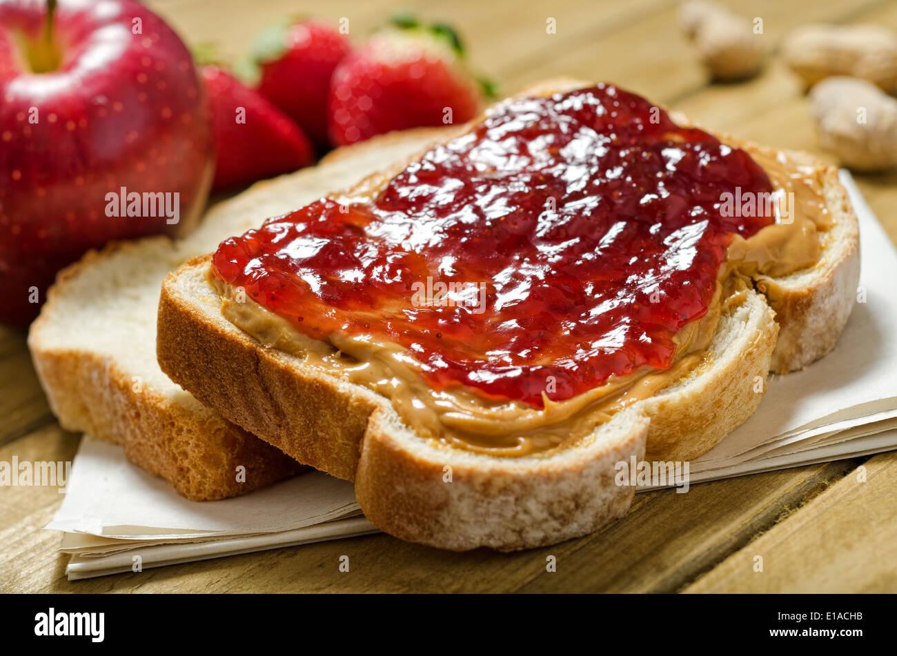 Eine nahrhafte Erdnussbutter und Marmelade-Sandwich mit Äpfel, Erdbeeren und Erdnüssen. Stockbild