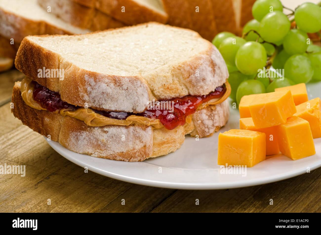 Eine nahrhafte Erdnussbutter und Marmelade-Sandwich mit Cheddar-Käse und Trauben. Stockbild