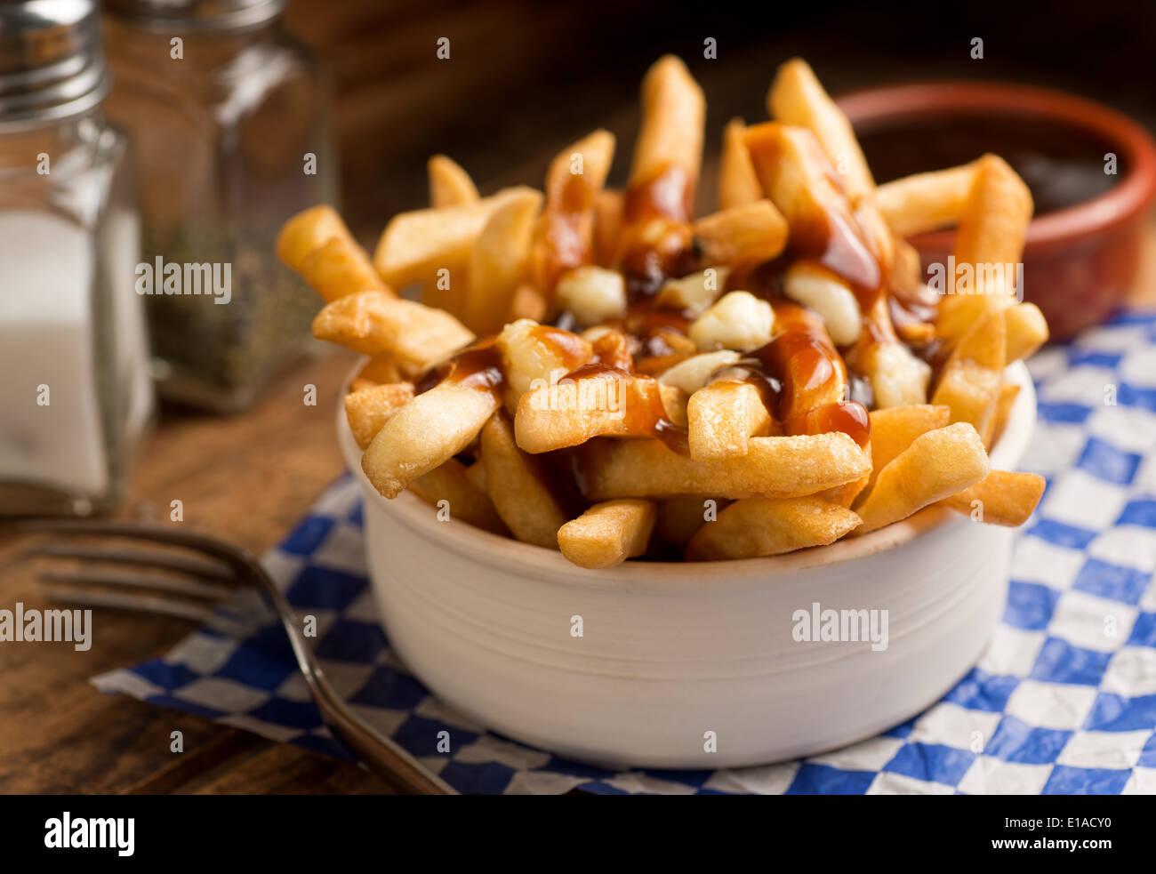 Klassische französische kanadische Poutine mit Pommes frites, Soße und Käse Quark auf einem rustikalen Tisch. Stockbild