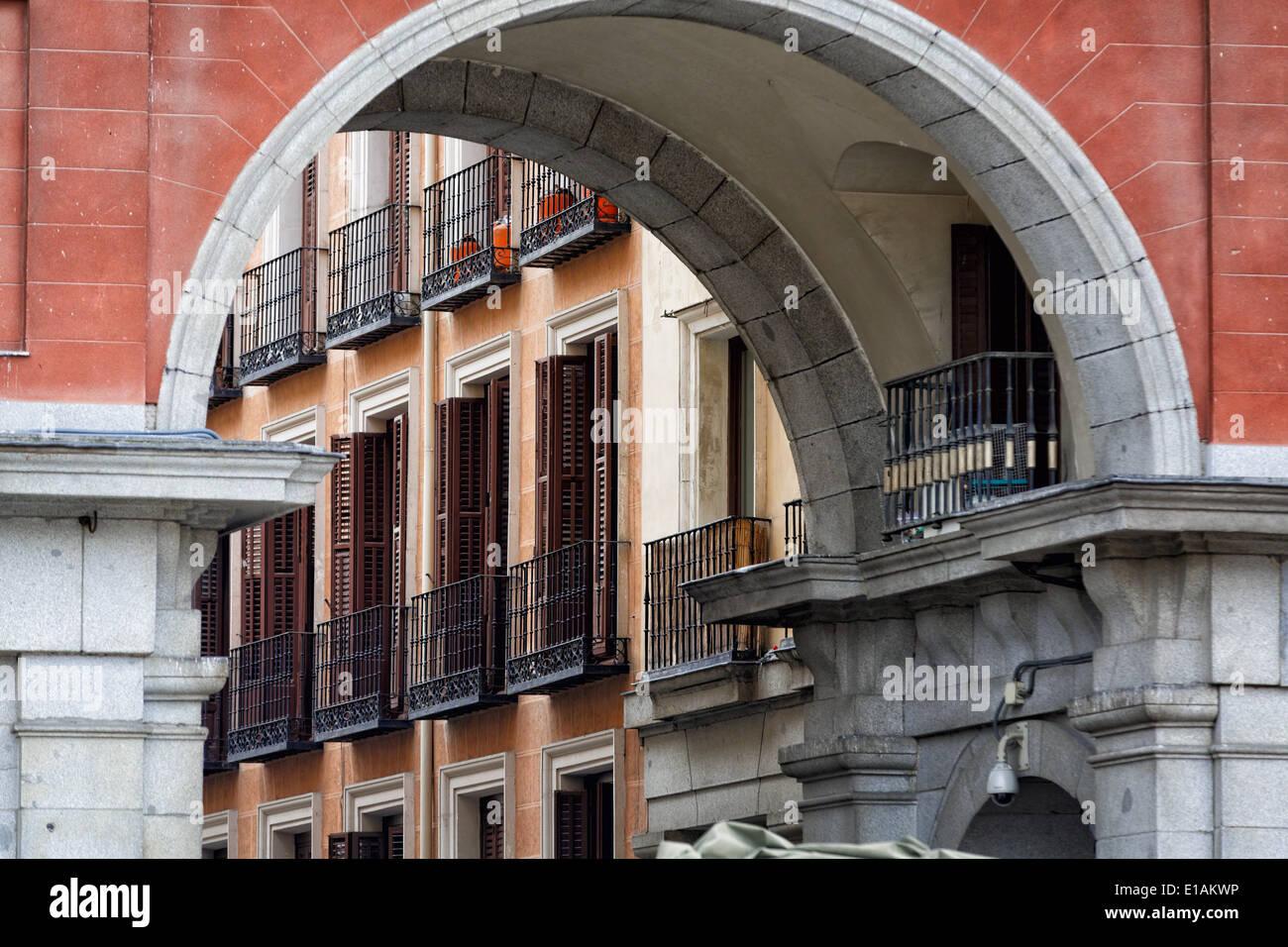 Balkone und Fenster mit Fensterläden, betrachtet durch einen Bogen von einem Gebäude, Plaza Mayor, Madrid, Spanien Stockbild