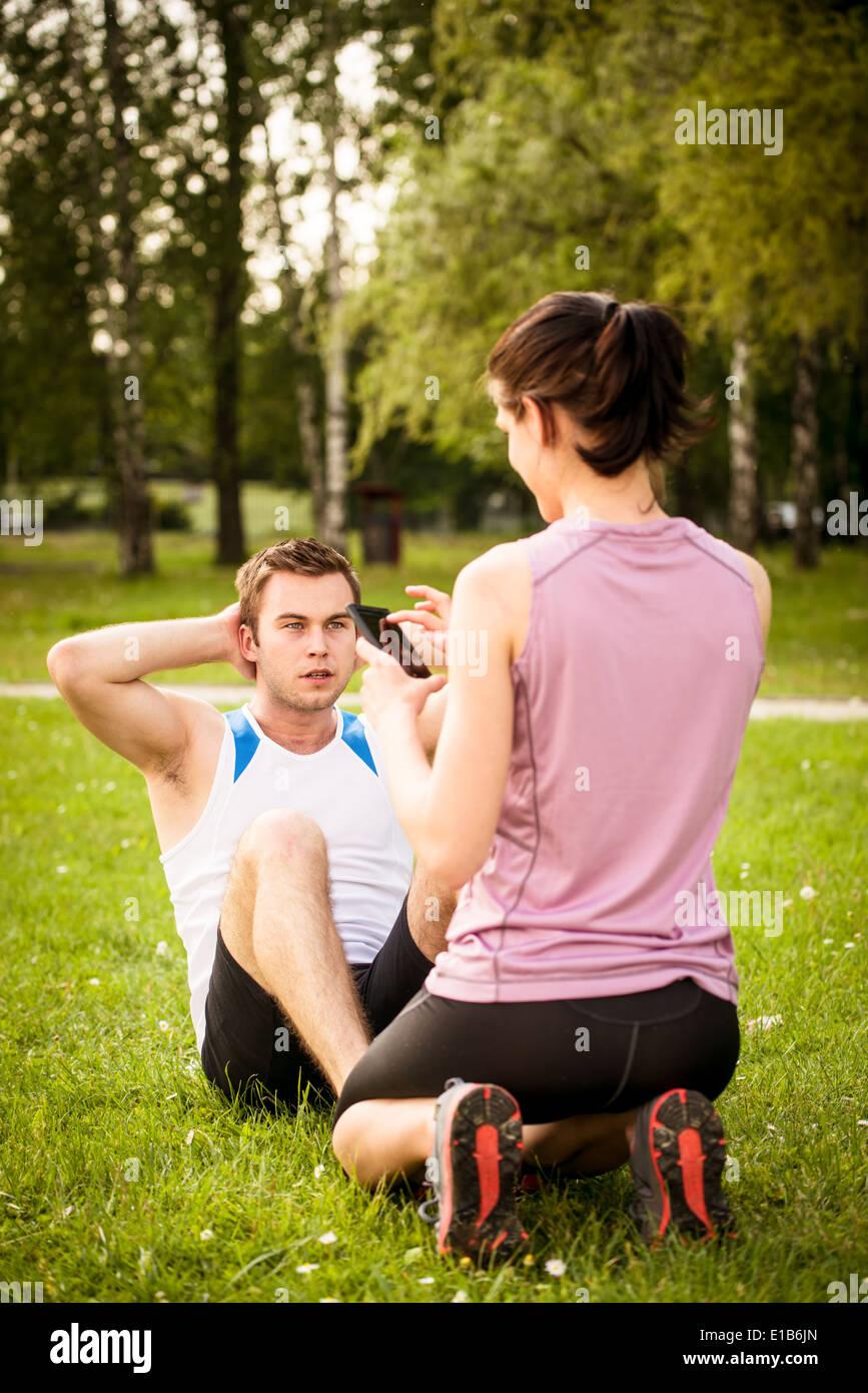 Mann macht Sit-ups, während Frau, Zeit der Übung auf dem Handy zusieht Stockbild