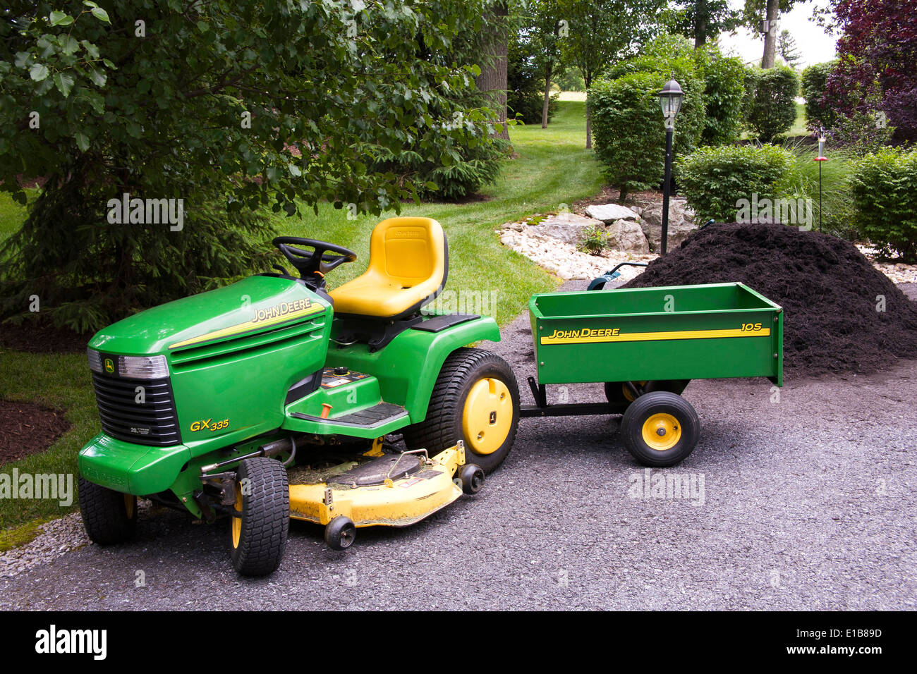 john deere traktor mit wagen vor haufen garten mulch in einem wohngebiet hinterhof stockfoto. Black Bedroom Furniture Sets. Home Design Ideas