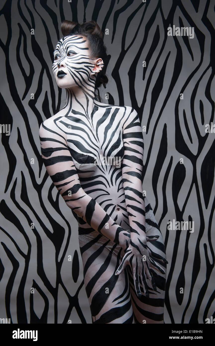 Eine Frau mit ihrem Körper lackiert in schwarz / weiß Zebra-Streifen an den Hintergrund anpassen Stockbild
