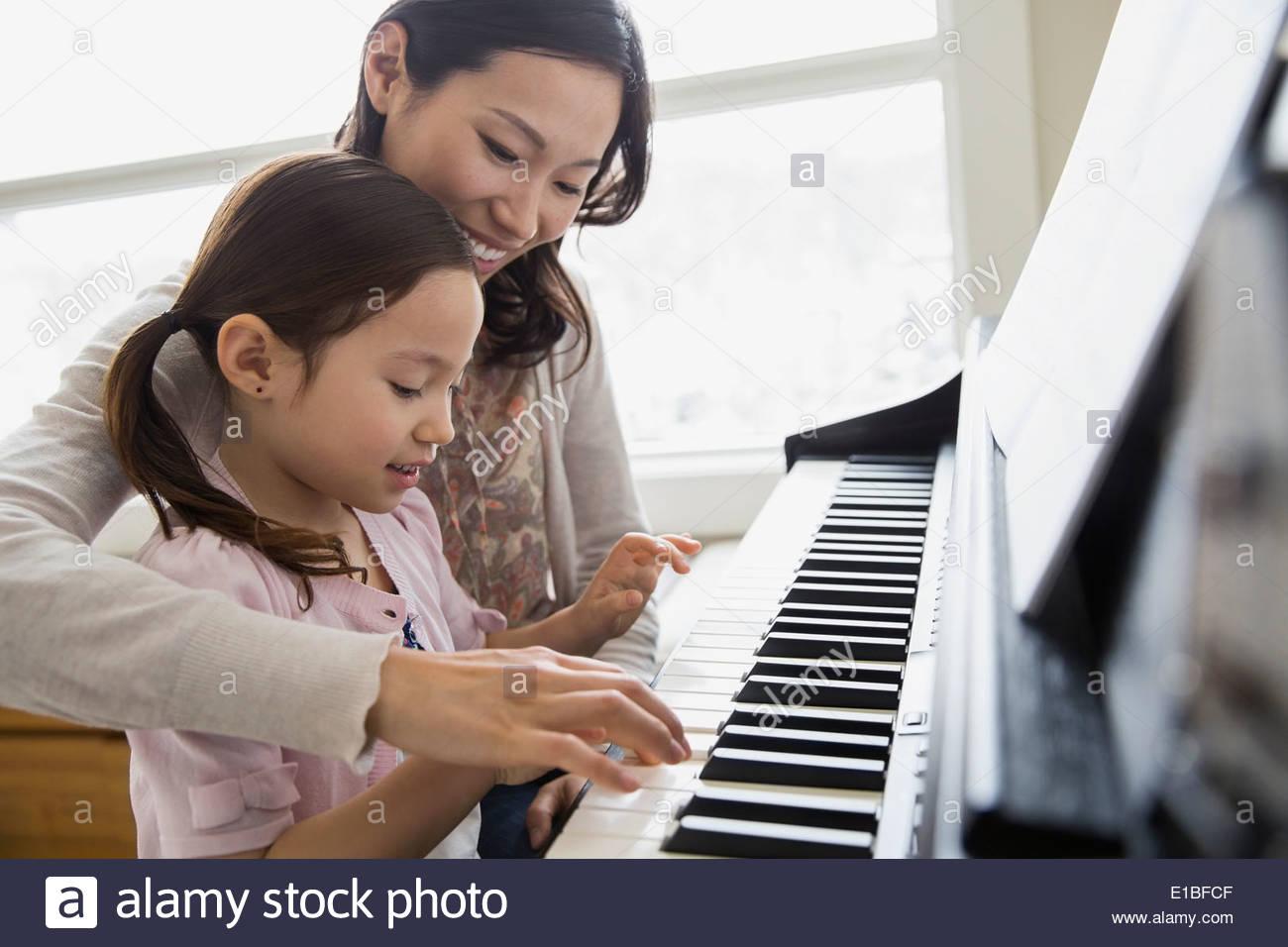 Mutter Tochter Unterricht, Klavier zu spielen Stockbild