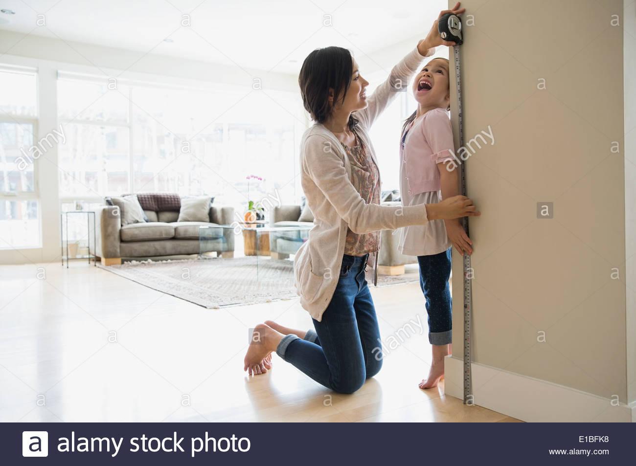 Mutter, die Messung der Höhe der Töchter im Wohnzimmer Stockfoto